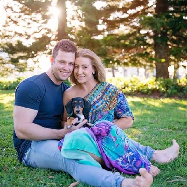 Brittany and Cory with their sausage dog Armani sitting on the grass