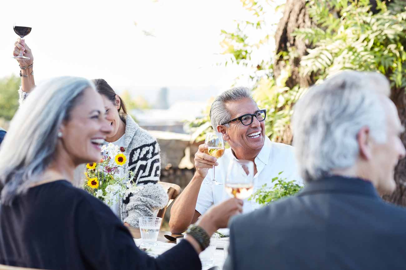group of seniors toasting together in an outdoor table