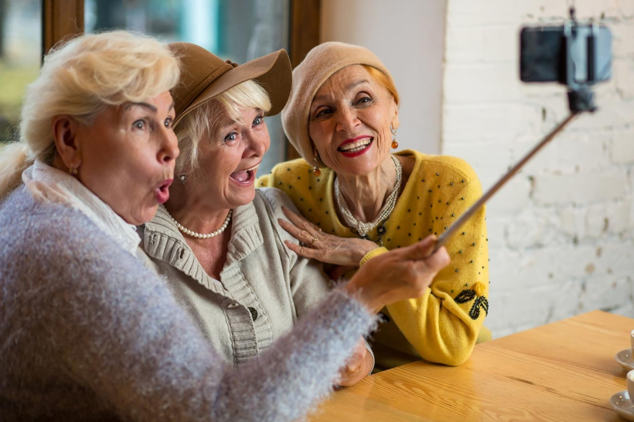 Three ladies having fun with a selfie stick.