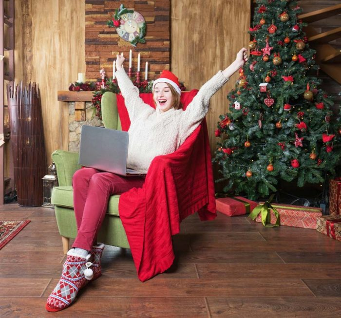 happy woman with laptop beside a christmas tree