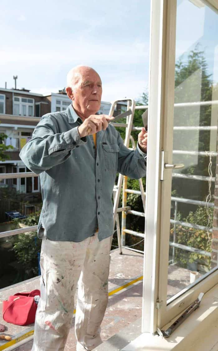 Elderly man paints a house