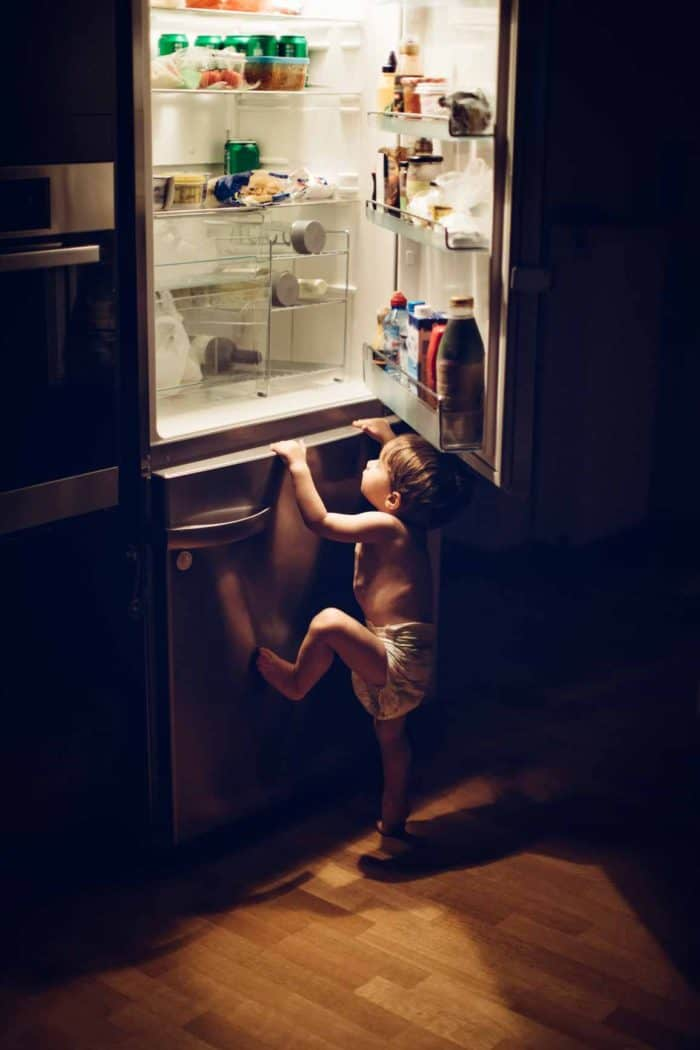 naughty kid trying to climb the refrigerator