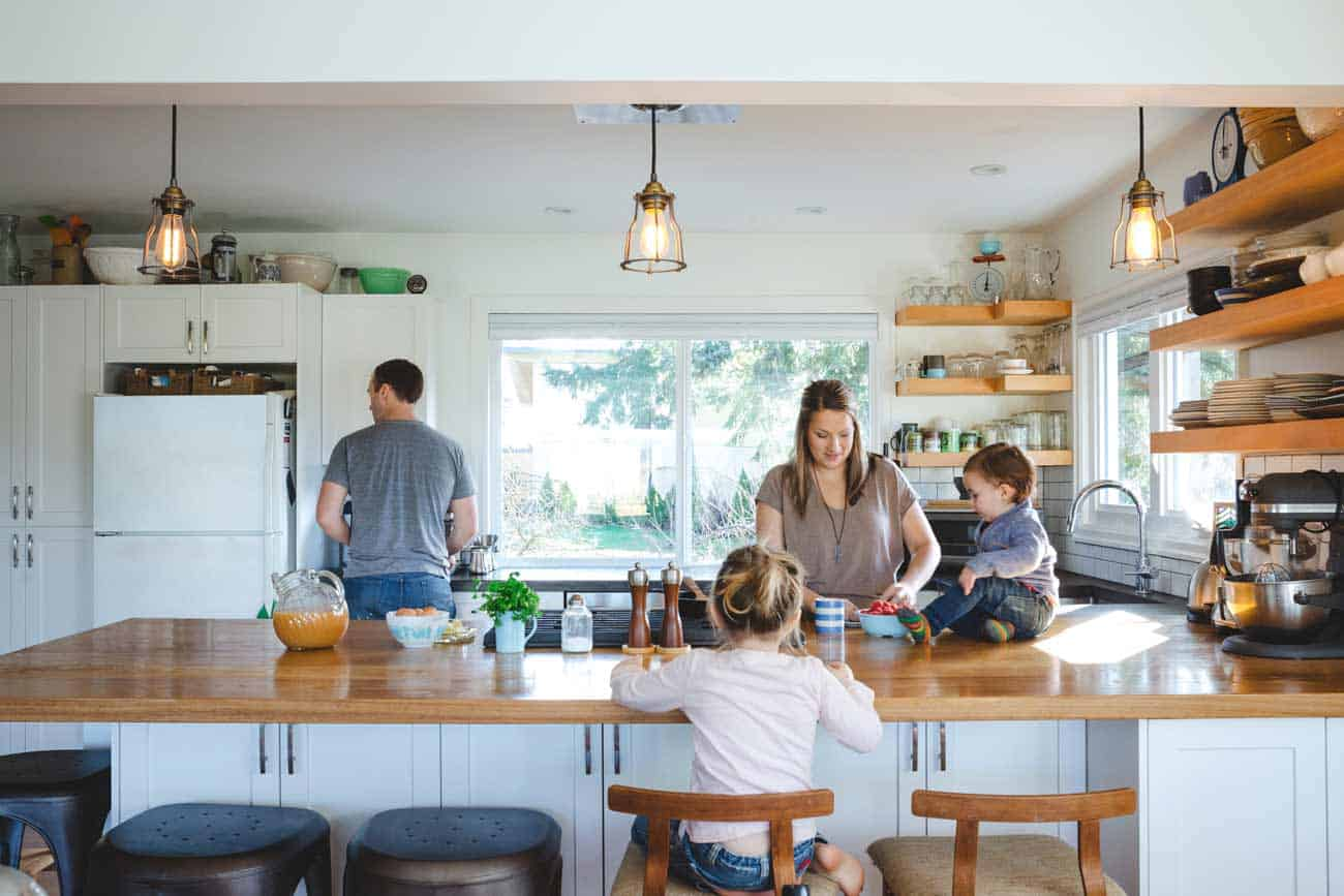 Cool, young family spending time together in bright, modern kitc