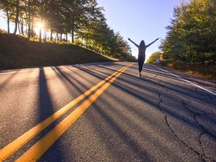 woman walking on the road feeling the freedom she has