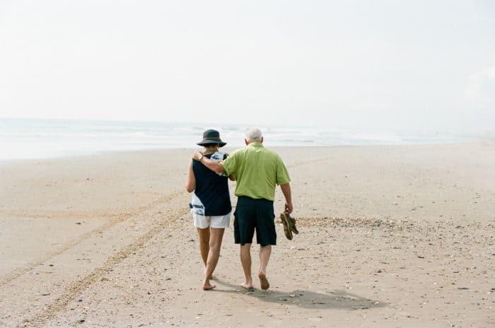 older couple walking on the beach